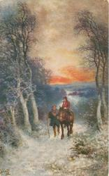 man walks beside woman riding horse front down snowy lane as sun sets
