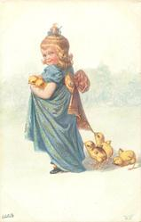 girl dressed in blue faces left, looks front holding two chicks, three others on ground peck at her skirt