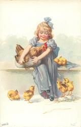 girl dressed in blue sits holding hen, five chicks around