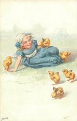 girl dressed in blue lies on grass with 6 chicks