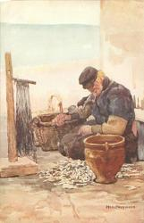 SERIES HOLLAND FISCHER VOLENDAM Dutch man sits on quay right hand on basket, looking down, smoking pipe