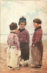 SERIES HOLLANDKINDER VOLENDAM three Dutch boys stand with hands in pockets, on sea-shore