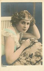 CASSIVE  woman with pearls around head, leans forward, right hand on cushion