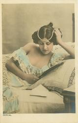 DERVAL  woman with pearls on head, lies in bed reading book