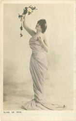 ELISE DE VERE  very tight hobbled dress, her right arm raised carrying flowers, looking left