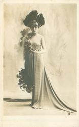 REGNIER  low cut dress, furry cape over her right shoulder, fancy hat, flowers to her right side