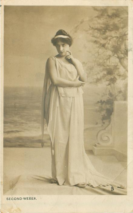 SEGOND-WEBER  woman on stage with long white wrap, hair up in back with white ribbon through hair