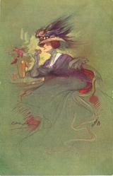 elegantly dressed woman with flowing skirt, elaborate hat with ostrich feather, sits by table with vase of flowers on it, holds flower to her face,facing & looking left, green background