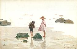 boy & girl stand on either side of rock, boy looks in pail, on the beach