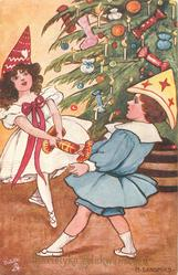 boy and girl  in fancy hats pull cracker in front of xmas tree