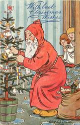 """THE LITTLE DEARS WILL BE SURPRISED!""  Santa puts toy on tree, golly in sack, two children peek!"
