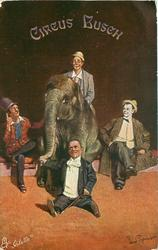 elephant seated centrally, one clown rides, midget sits front holding trunk, clown on each side