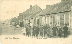 UNE RUE DE MIQUELON  low houses right, people close