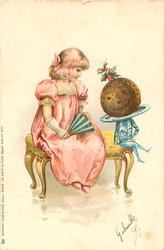 girl in pink sits talking to a personised Christmas pudding