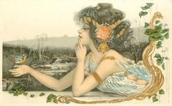 girl reclining on stomach, looking at bird resting on her right hand