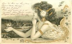 girl reclining on stomach,looking at bird resting on her right hand