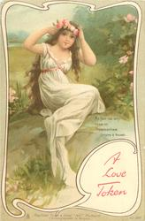 girl in white gown sits on rock adjusting floral garland in her hair