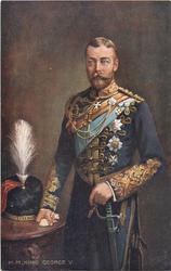 H.M. KING GEORGE V.  in military uniform, helmet on table