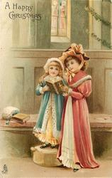 A HAPPY CHRISTMAS  two girls stand reading open bible