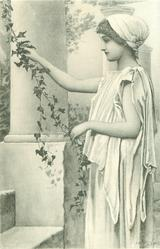 short haired brunette stands holding ivy vine, facing & looking left