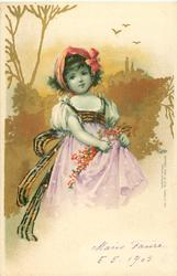 young girl in white top, red scarf round her hair, holds flowers in violet skirt, faces slightly right, looks front