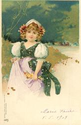young girl in green/white dress holds flowers in violet skirt, faces left/front