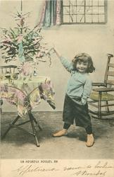 UN HEUREUX NOUVEL AN  small boy stands with feet apart pointing to Xmas tree on table