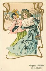 two pretty women in old style dresses walk left/front in snow, one wears muff