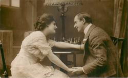 young lovers sit at table with board behind them, they hold hands