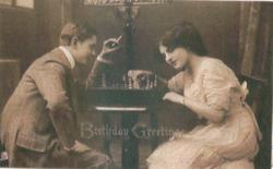 young lovers sit at table with board between them, he is to the left & is smoking