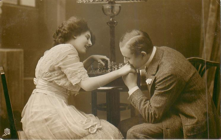 young lovers sit at table with board between them, man kisses womans hand