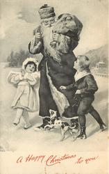 A HAPPY CHRISTMAS TO YOU  Santa with sack has boy to his left, girl right, dog in front