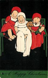 A HAPPY CHRISTMAS, three children sitting on bench, left and right in dressed in red, middle child in white, dachshund between them, black background