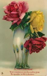 tall teal & cream vase with peacock feather design, one pink rose left, one red and one yellow rose right