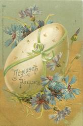 enormous egg tied with green ribbon, blue cornflowers around