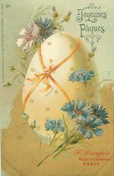 enormous egg tied with orange ribbon, blue & one white cornflowers around