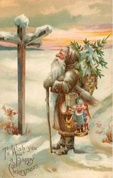 TO WISH YOU A HAPPY CHRISTMAS  Santa, in snow, carrying toys & tree, looks at signpost