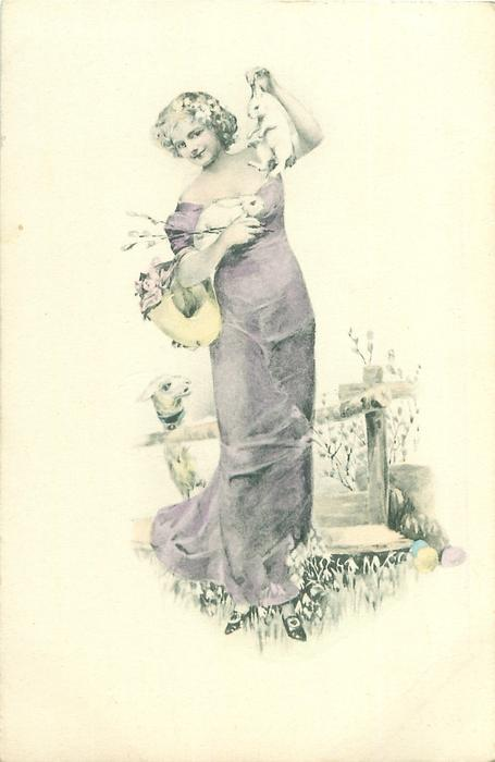 woman stands facing front holding two rabbits, lamb below back