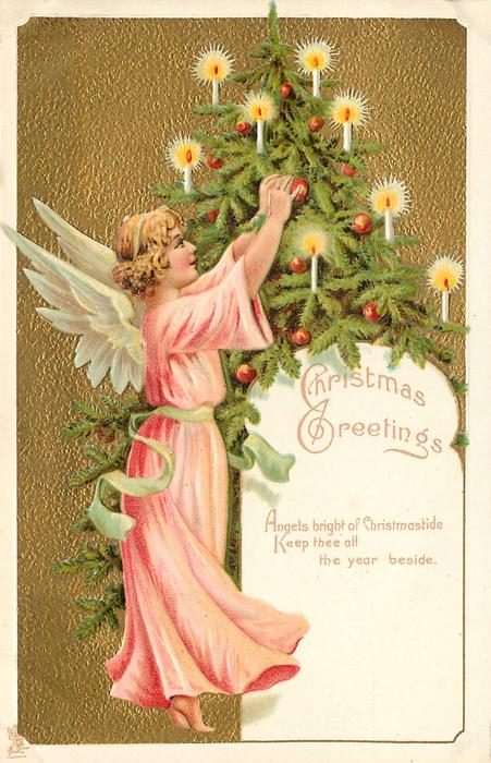 CHRISTMAS GREETINGS     angel in deep pink robe to left of Xmas tree reaches up to adjust ornament