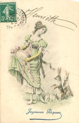 girl in old style dress carries large Easter egg in her skirt & looks down at three rabbits