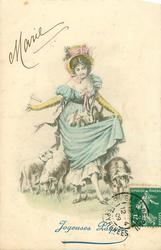 girl in old style dress stands carrying 3 rabbits in her skirt, two sheep & a lamb around