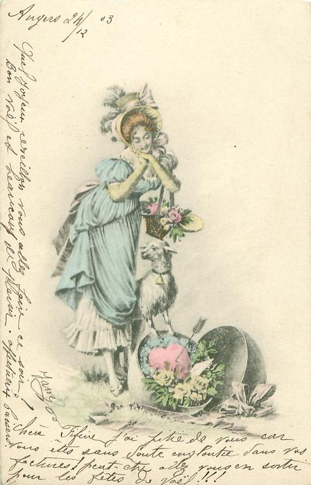girl in old style dress stands looking down at lamb standing up on a large Easter egg containing a heart with arrow in it