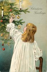 CHRISTMAS GREETINGS  girl in white gown reaching up to ornaments on tree