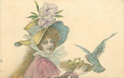 woman wearing elaborate hat carries birds nest with chicks & bird alighting, faces right, looks front