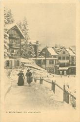 snow scene, man & woman walk front along path at left, tall houses & shops behind
