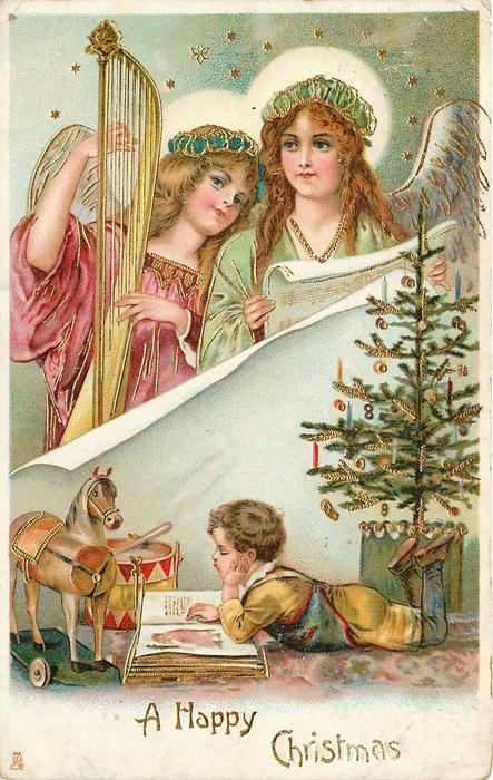 A HAPPY CHRISTMAS  two angels above, one with harp, boy reads in front of wooden horse below, Xmas tree to right