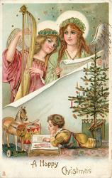A HAPPY CHRISTMAS, two angels above, one with harp, boy reads in front of wooden horse below, Xmas tree to right
