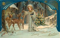 LOVING CHRISTMAS WISHES angel stands giving food to three deer, Christmas tree behind, ornate blue border above