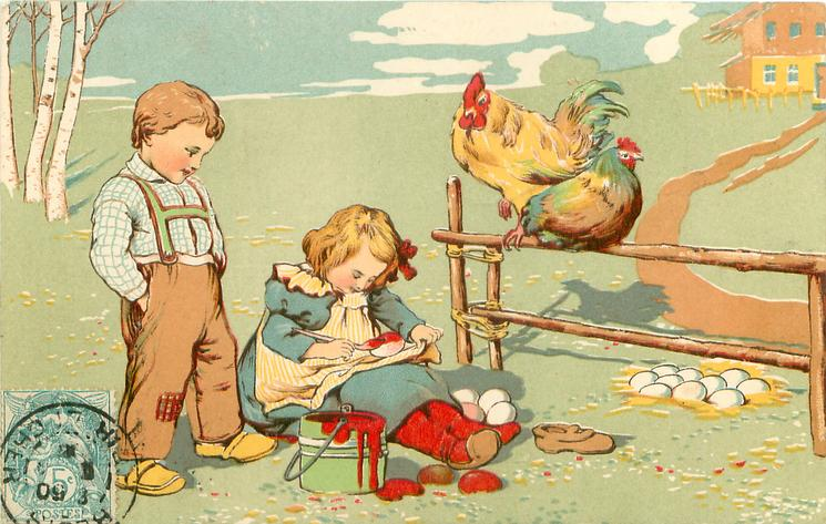 girl sits painting an Easter egg, boy stands & observes, cock & hen sit on rail