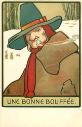 UNE BONNE BOUFFEE man in pale brown coat , green hat, smoking upside down pipe outdoors in snow, faces left looks front